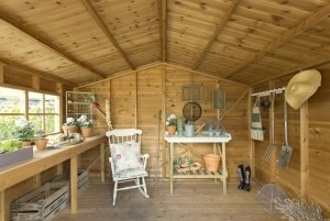 The interior of a decorative potting shed with georgian windows and a workbench