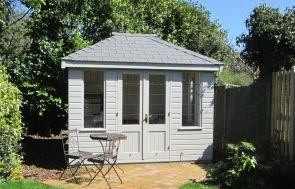 Cley Summerhouse with a hipped roof covered in slate-composite tiles and a shiplap clad exterior painted in pebble paint. There are leaded windows showing into the lined interior. It is placed in a picturesque garden with a small dining table and chairs and hedges.