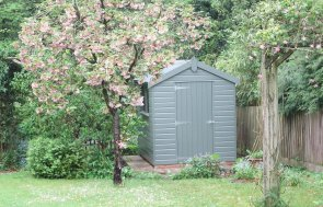 A Classic Garden shed with an apex roof covered with felt. The shed is clad with shiplap timber and painted in the shade of Stone. It has a single door entry and two windows.