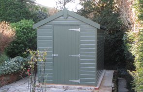 A classic garden shed with an apex roof and single door entrance. The exterior is clad with shiplap timber and painted in Stone