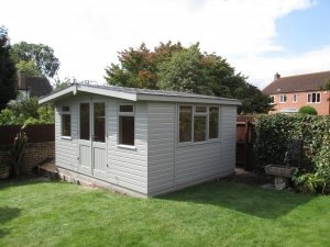 A garden studio with an apex roof covered in slate composite tiles. The exterior is clad with smooth shiplap timber coated with pebble paint and the windows are all desk-height.