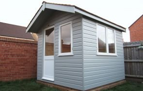 The exterior of a small Binham Studio painted in two-tone ivory and pebble paint. The roof is apex with a small overhang and covered with slate composite tiles.