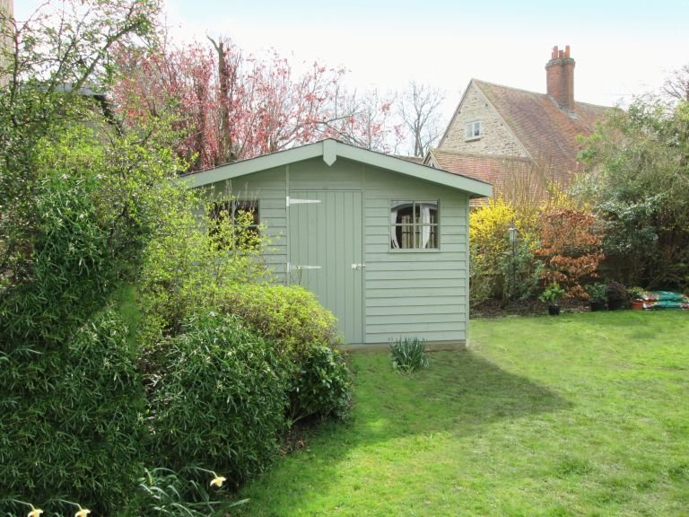 An attractive garden shed nestled in a well-kept garden partially concealed behind shrubbery. The apex roof is covered in heavy-duty felt and has a slight overhang on the gable.
