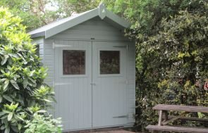 The gable end of a superior shed with double doors and plain windows. The apex roof is covered with heavy-duty felt and has a slight overhang.