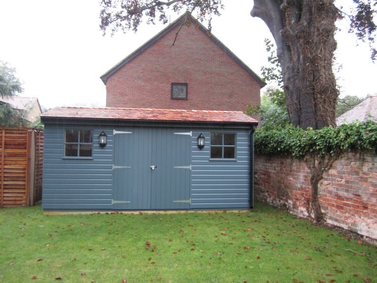 A large superior shed in a dark slate paint and shiplap cladding. It has an apex roof covered with cedar shingles, double door entry and georgian windows.