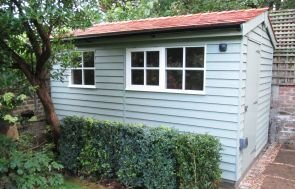 An apex garden shed clad with rustic weatherboard and boasting an apex roof covered with terracotta tiles. The shed has been painted in a two tone fashion with contrasting window and door frames.