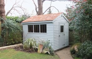 An appealing garden shed with attractive weatherboard cladding and an apex roof covered with cedar shingles.