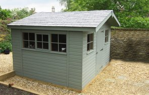 An apex garden shed with a slate covered roof and an overhang on the gable. There are Georgian windows and double door access.