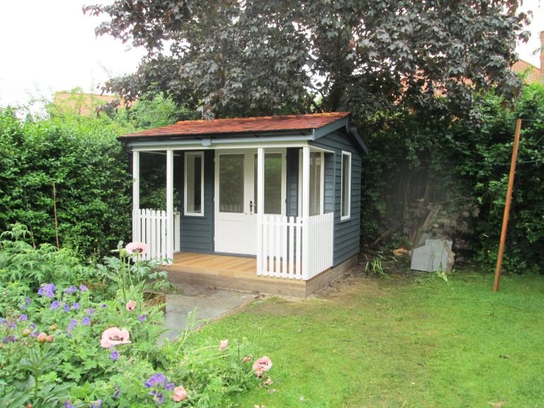 A small and compact pavilion garden room with an apex roof covered in cedar shingles and with black guttering along the fascia boards. The building is clad with rustic weatherboard and enjoys double access doors and several windows.