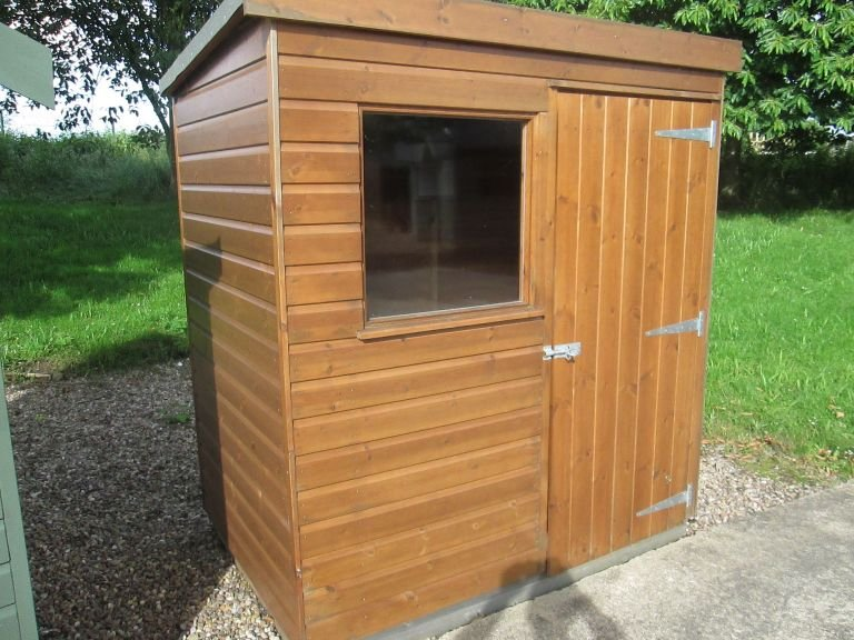 1.2 x 1.8m  Sikkens Walnut stained Classic Shed designed with a single door with window and a pent roof covered in heavy duty felt
