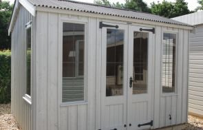 A National Trust Lavenham Summerhouse exterior shot taken at a showsite location. The building has an apex roof covered with corrugated material and cast iron door furniture which complements the traditional leaded windows and double doors.