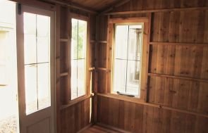 The interior of a National Trust Lavenham Summerhouse showing leaded windows and wooden walls.