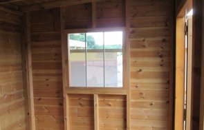 The natural pine interior of a National Trust Flatford Summerhouse with leaded windows.