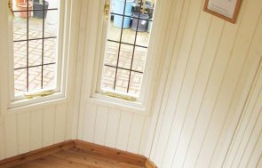 The interior of a Wiveton Summerhouse that has painted interior lining and leaded windows with brass door furniture.