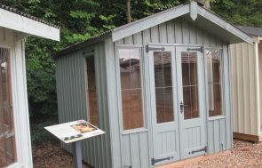 Ickworth National Trust Summerhouse with vertical cladding and an apex roof with corrugated covering. The summerhouse has leaded windows and cast iron door furniture and is painted in Terrace Green.