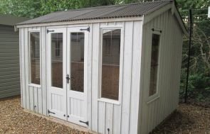 National Trust Lavenham Summerhouse with an apex, corrugated roof and leaded windows. There is vertical timber cladding painted in earls grey.