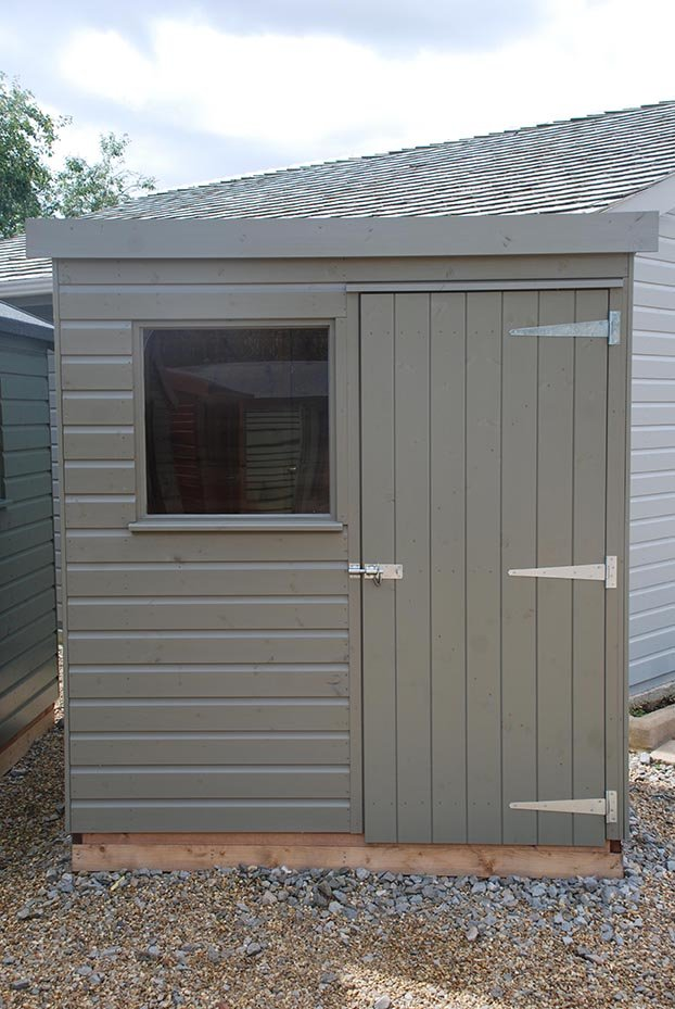 A small 1.2 x 1.8m Classic Shed with a pent roof covered in heavy-duty felt and shiplap cladding on the exterior painted in Stone.