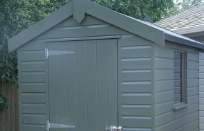 A 1.5 x 2.1m Moss-painted Classic Shed with an apex roof and door in the gable
