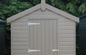 A classic shed painted in Stone and clad with timber shiplap. It has an apex roof covered with heavy-duty felt and a single access door in the gable.