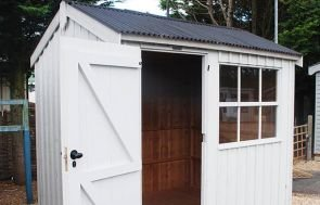 An attractive National Trust Felbrigg Shed with an open door showing the natural wood interior. The shed has vertically-sawn cladding and a window with Georgian bars. The apex roof is covered with corrugated material.