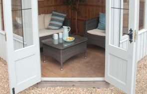 An image showing both the exteiror and interior of the orford summerhouse thanks to the double doors being pinned open and a decorated interior visible. There is a table and chairs set up as well as a coffee table and house plant.