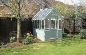 A Greenhouse painted in the Sage exterior colour in an attractive garden surrounded by small shrubs and trees.
