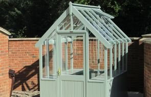 A small greenhouse painted in the exterior shade of lizard on a garden patio within a walled garden.