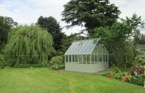 A large greenhouse pictured in a generously sized garden with a grassy lawn, flowering vegetable patch and a willow tree. The greenhouse is painted in the exterior colour of Lizard green.