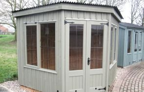 An orford summerhouse pictured on one of our showsite centres where the side profile of the pent roof is visible along with the leaded windows and vertical cladding. The door furniture is cast iron material,.