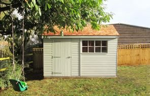 A medium sized garden shed perched in an attractive garden with a grassy lawn and childrens swing in a tree. The building has an apex roof covered with cedar shingles and two georgian windows. The exterior of the shed is clad with smooth shiplap.