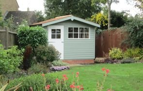 An attractive shed situated in the corner of a decorative garden with red flowers and shrubbery. The shed has an apex roof covered with cedar shingles and a slight overhang. The door and windows are painted ivory while the rest is painted in Lizard. The shed is clad with rustic weatherboard.