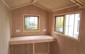 The interior of a lined and insulated superior shed with a workbench and security pack. The shed has an apex roof and two opening windows.