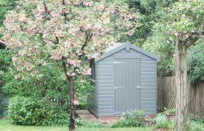 An attractive garden shed painted in moss situated in a pretty garden beneath a large blossom tree. The building has an apex roof covered with heavy-duty, heat-bonded felt and smooth shiplap cladding painted in the green shade of moss.