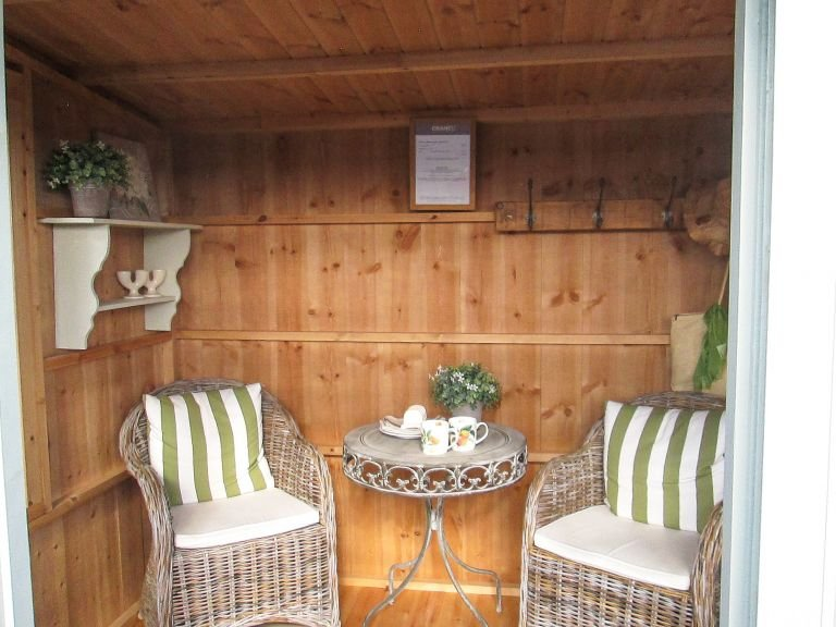 An Internal shot of a Flatford summerhouse showing two garden chairs and a table between them inside the building
