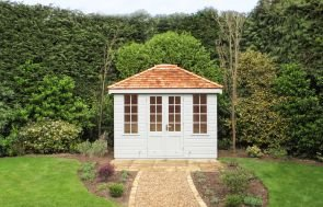 A classical, hipped roof summerhouse with shiplap cladding and georgian windows. The roof is covered with cedar shingles and the exterior cladding with our exterior paint in the shade of Saltwater.
