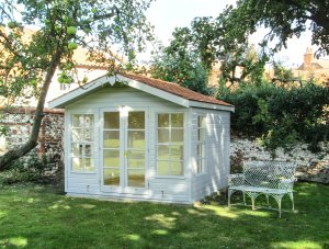A chalet-style blakeney summerhouse in a stunning walled garden with trees and an antique outdoor bench. The summerhouse has an apex roof covered with cedar shingles and smooth shiplap cladding painted in ivory.