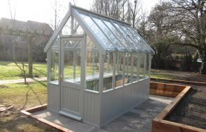 A greenhouse pictured on a sunken patio surrounded by raised vegetable and planting beds. The greenhouse is painted in the exterior shade of pebble, which is a warm grey.
