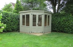 The national trust orford summerhouse pictured on a patio area in someones well-kept garden with a large grassy lawn. The summerhouse features a pent roof covered in corrugated material and leaded windows.