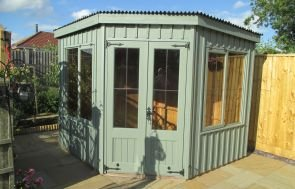 NT Orford Summerhouse in Terrace Green, situated in a corner plot of someones garden. The summerhouse has a pent roof and a distinctive shape to help it fit into corners.