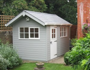 The exterior of a small and appealing garden shed. It has an apex roof covered with slate tiles and a small overhang on the gable where there is a white birdbox. There are two visible sets of windows that all feature georgian bars. There is white guttering along the fascia boards and the building is painted in a light gray shade and ivory.
