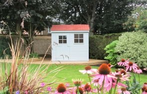 A small superior shed in a large garden with piink flowers in the foreground. The shed has an apex roof covered with terracotta tiles and smooth shiplap cladding painted in sage exterior paint.