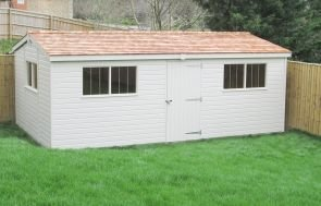 A large shed in the light paint shade of Cream, with an apex roof covered in cedar shingles and a single access door in the length.