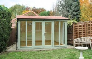 Attractive garden studio with terracotta roof tiles and floor-to-ceiling windows. it has electrics and painted interior