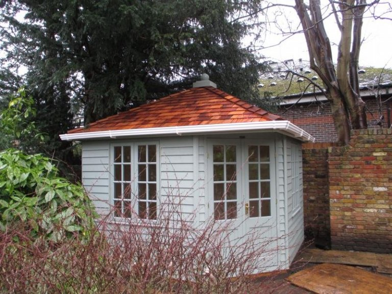 Corner summerhouse with a hipped roof covered in cedar shingles with white guttering. It is clad with weatherboard and painted in a light grey colour. The windows have georgian bars.