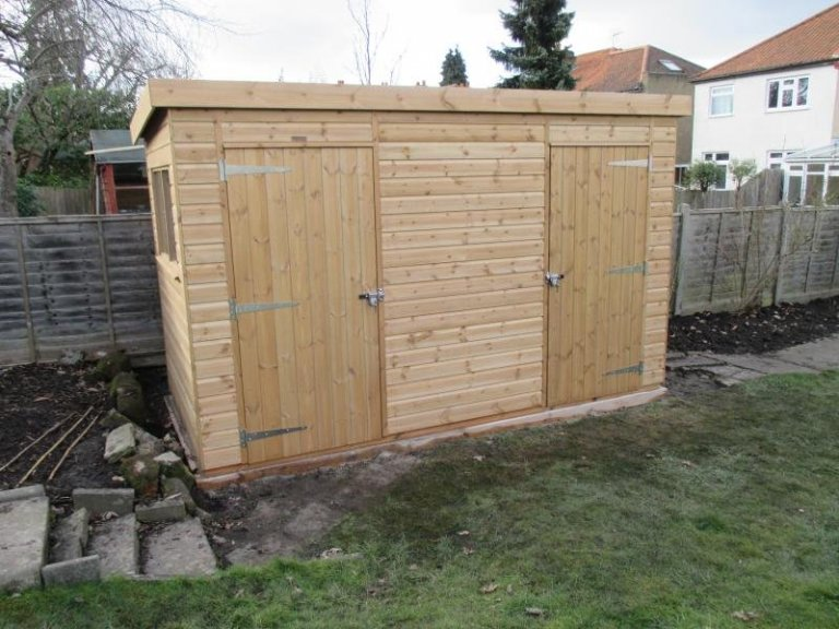 A pent timber garden shed with two single access doors and internal partition.