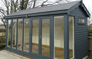 A stylish garden studio in slate with scalloped fascias and painted interior. The studio has floor-to-ceiling windows.