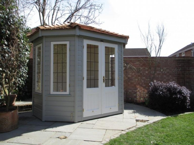 An insulated summerhouse with leaded windows and two-tone exterior paint. Octagonal summerhouse with shiplap cladding,