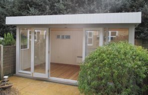 attractive modern garden studio with floor-to-ceiling windows and painted interior.