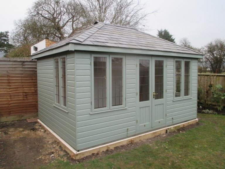 large summerhouse with hipped roof covered in grey slate tiles. Building is clad in shiplap with leaded windows and painted interior.