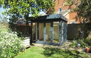 Attractive modern garden studio with pent roof and floor-to-ceiling windows painted in Slate shade.
